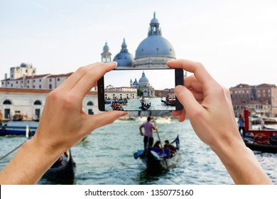 Taking pictures on mobile smart phone in Gondola on Canal Grande with Classic old house in the background, Venice, Italy