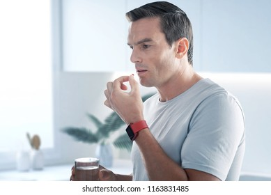 Taking pills. Handsome young man standing with a glass of water and taking pills while having an unbearable headache