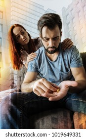 Taking pills. Tired young ill man sitting on the sofa with necessary pills in his hand and feeling terrible while his attentive kind girlfriend sitting behind his back and feeling worried