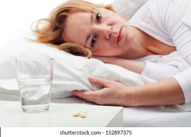 Taking pills - woman laying in bed with medication prepared on the night stand