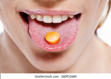 Taking pills. Woman taking pill. Pill on her tongue / close-up of young woman holding pill on her tongue - isolated on white background