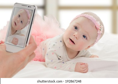 taking portrait of six month old baby girl in pink dress. on window background
