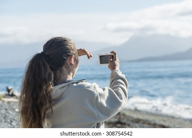 Taking a selfie with her phone in Homer, Alaska