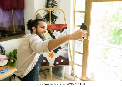 Taking a selfie with my painting. Cheerful latin man posting a picture on social media of his artwork
