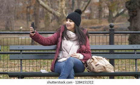 Taking a selfie while relaxing on a bench at Central Park
