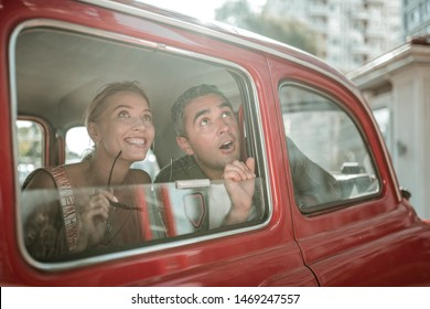 Taking in the sights. Admiring husband and wifee looking at the city sightseeings out the window of the car.