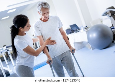 Taking steps. Calm attentive aged man feeling worried while taking steps with a help of crutches and looking on the floor while attentive qualified specialist controlling this process