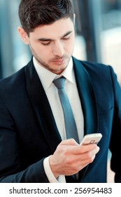 Taking time for coffee break. Confident business man in suit drinking coffee and typing a message on mobile phone while sitting in restaurant