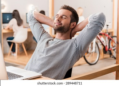 Taking time for a minute break. Cheerful young man holding hands behind head and keeping eyes closed while sitting at his working place with his colleagues working in the background