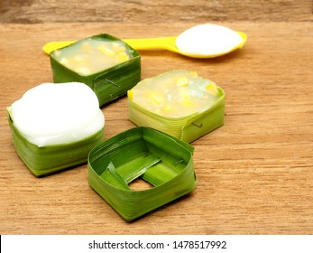 """""""Tako"""" is a traditional Thai pudding. First layer is flour mixing with corn and topped by coconut mix. Wrapping the dessert by pandan leaves. Selective focus at a pandan wrap and coconut topping."""