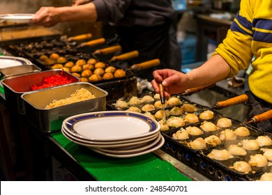 Takoyaki being grilled at a street food stall in Osaka, Japan.