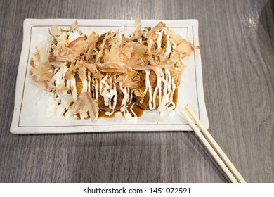 Takoyaki, fried Japanese octopus ball on white plate and wood table