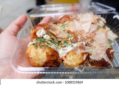 Takoyaki japanese food Octupus Balls on Woman Hand
