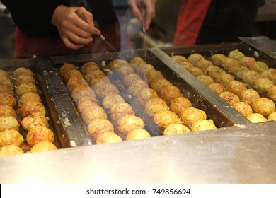 "Takoyaki on a hot pan. Japanese snack in the shape of little round balls containing pieces of octopus inside, some people call it ""Octopus Balls"" or ""Octopus Dumplings""."