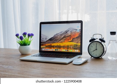 TAK,THAILAND - NOV 10,2018 : Wood Office table with Macbook Pro retina 13 inch with macOS High Sierra Screen, retro clock, beautiful purple flower and bottle of water.