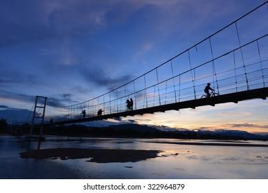 TAK,Thailand-June 18, 2015:Sunset landscape at The old wooden bridge(Mon bridge ) across the Ping river at Tak Province, Thailand