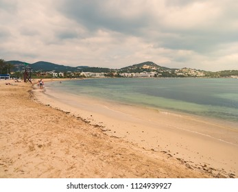 Talamanca beach in the city of Ibiza, Spain. People relaxing in the sand or bathing in the sea. Stormy summer day