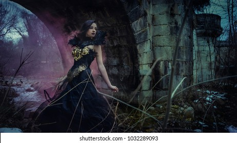 Tale, Beautiful brunette woman with gothic dress made in gold and black threads. It is in a snowy forest in winter. fantasy concept