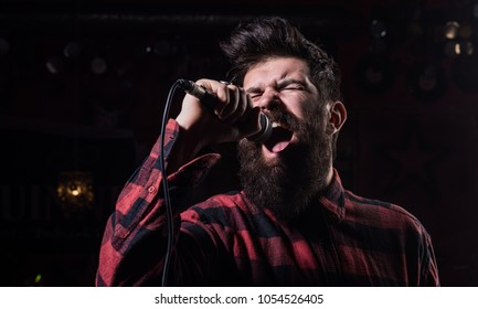 Talent show concept. Musician with beard and mustache lighted by spotlight. Musician, singer singing in music hall, club. Man with tense face holds microphone, singing song, black background.