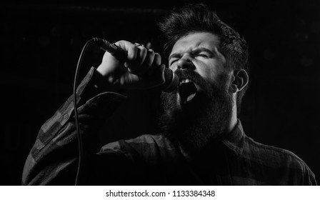 Talent show concept. Musician, singer singing in music hall, club. Man with tense face holds microphone, singing song, black background. Musician with beard and mustache lighted by spotlight.