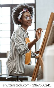 Talented artist. Creative talented African-American artist sitting in front of drawing easel and painting