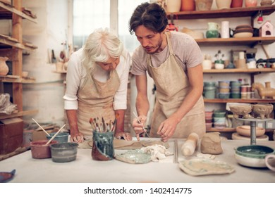 Talented artist. Handsome young man standing near the aged woman while showing her how to paint
