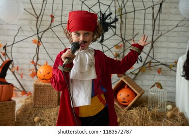 Talented boy in pirate costume singing in microphone at Halloween party