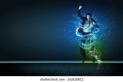 Talented cheerful businessman jumping with glowing energy lines on background