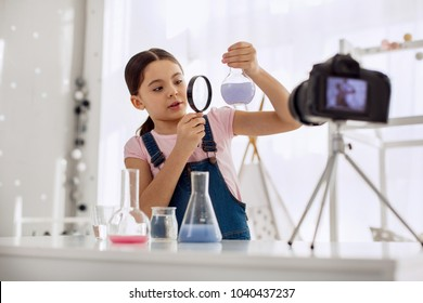Talented chemist. Lovely pre-teen girl looking at a flask with a chemical in it through a magnifying glass while recording herself for a video blog