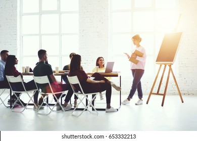 Talented coach young woman conducting productive training with male and female students about successful cooperation sitting in office indoors.Copy space area for your advertising text message