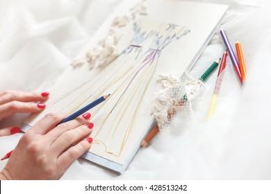 Talented dressmaker is designing bridal clothing