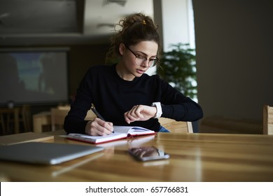 Talented female writer in stylish eyeglasses noting some information in notepad while looking on alarm watch to managing time for organization of working process sitting in university indoors