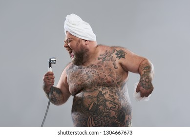 Talented funny fat man closing his eyes and singing with shower head in one hand while standing isolated on the grey background