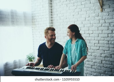 Talented girl teaches redheaded father playing synthesizer. Fatherhood. Child education concept.