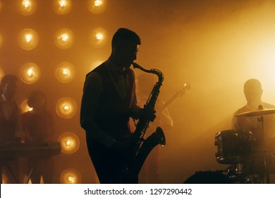 talented saxophone player.silhouette of man playing the saxophone.close up side view photo. hobby, interest, lifestyle