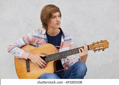 Talented teenage boy with trendy hairdo wearing shirt and jeans holding acoustic guitar playing his favourite songs while sitting against grey concrete wall, People, talent, lifestyle, music concept