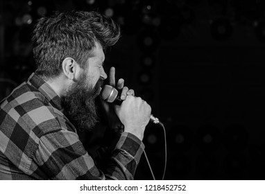 Talented vocalist concept. Man on tense face holds microphone, singing song, black background, copy space. Musician, vocalist with beard and mustache lighted by spotlight.