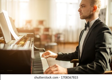 talented young caucasian pianist man practicing, perform awesome music. musician in formal elegant suit play piano