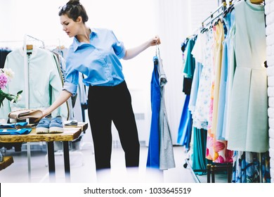 Talented young designer choosing clothing for new future collection standing in own showroom.Successful dressmaker holding hangers with trendy garment in hands and working on better variant of outfit