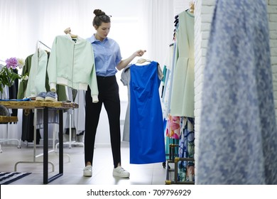 Talented young designer choosing clothing for new future collection standing in own showroom.Successful dressmaker holding hangers with trendy garment in hands and thinking on better variant of outfit