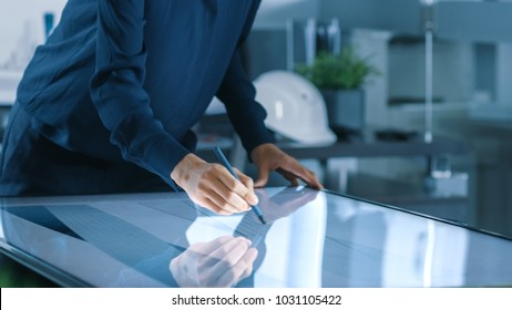 Talented Young Female Architectural Designer Draws Building Concept on a Graphics Tablet Display Vertical Touchscreen Table. Clean Minimalistic Office, Concrete Walls Covered by Blueprints.