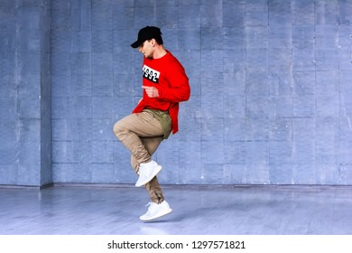 Talented young rapper in movement. Fashion style young boy dancing rap on beton wall background. Hip-hop street perfomance.
