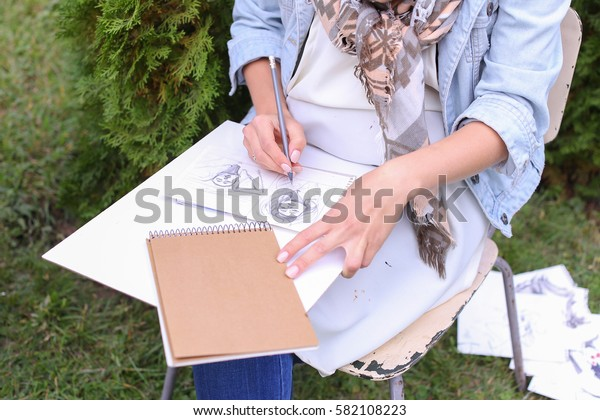 Talented Young Woman Handles Details ,obscures Hair in Picture. Sketch Executed Ordinary Pencil on Sheet of Paper Graphical Way, Which Lying on Wooden Tablet on Artist Knees, Which Located in Park in