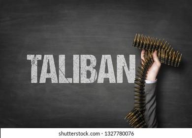Taliban text on blackboard with businessman hand holding ammunition