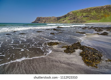 Talisker Bay, Isle of Skye, Scotland - Sandy beach with seaweed in the foreground and white surf and sea cliffs in the distance