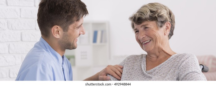 Talk between smiled senior woman and her young male carer