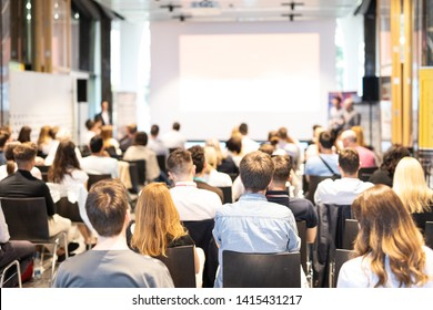 Talk in conference hall at business event. Audience at the conference hall. Business and Entrepreneurship concept. Focus on unrecognizable people in audience. Copy space on empty white screen.