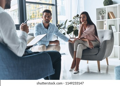 Talk out your problem. Young married couple talking while sitting on the therapy session with psychologist