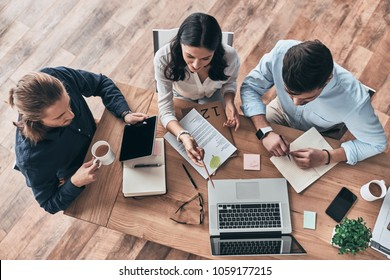 Talking about business details. Top view of young modern colleagues in smart casual wear working together while spending time in the office