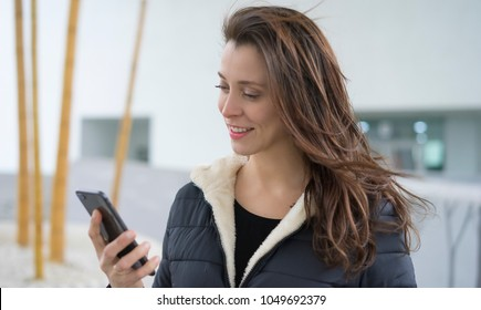 talking, Brown-haired woman in video conference with the mobile. talking on the street with your partner through the use of new technologies